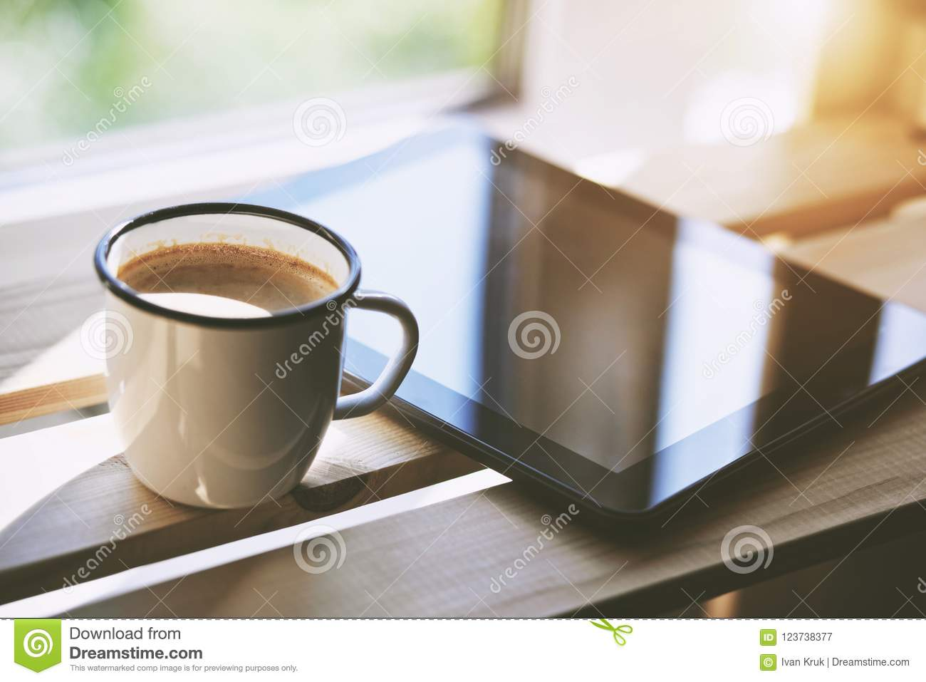Cup of coffee with tablet computer