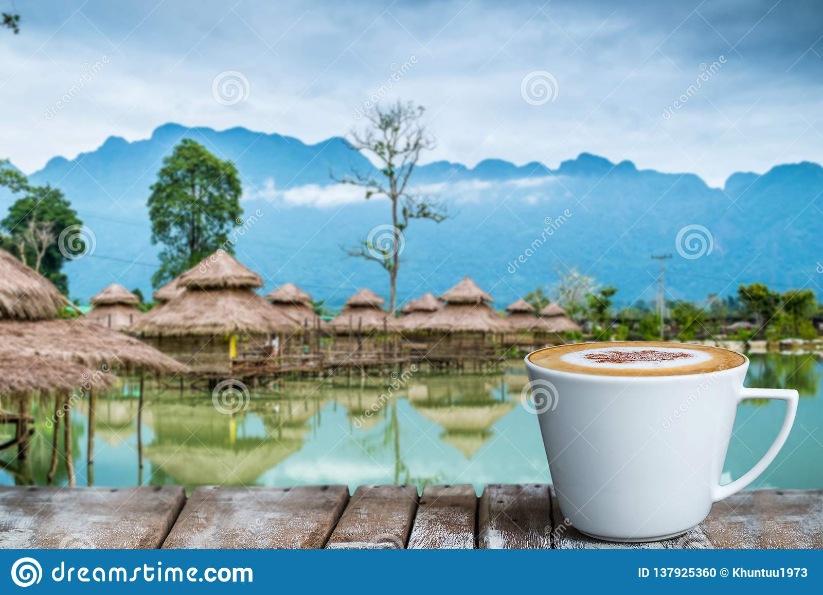 A cup of coffee on the wooden table by the lake
