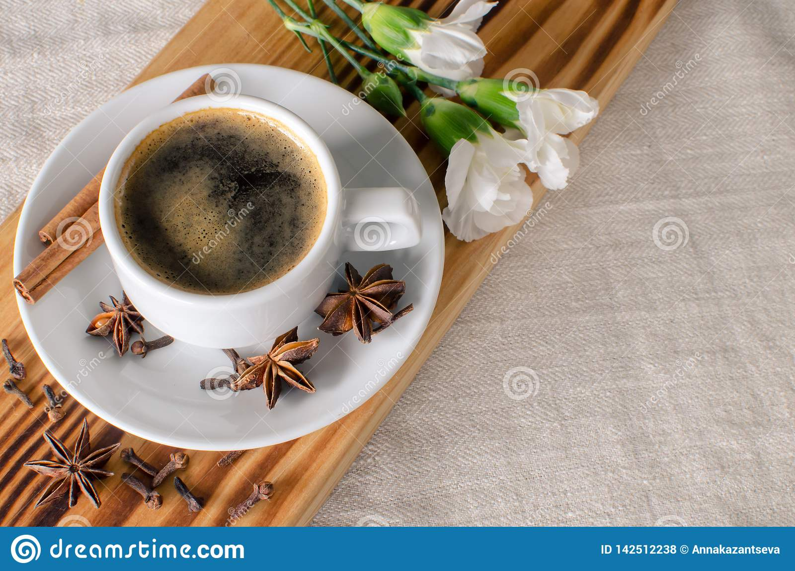 A cup of espresso, cinnamon sticks, anis stars and white carnations on wooden desk and textile background.  Good morning! Copy