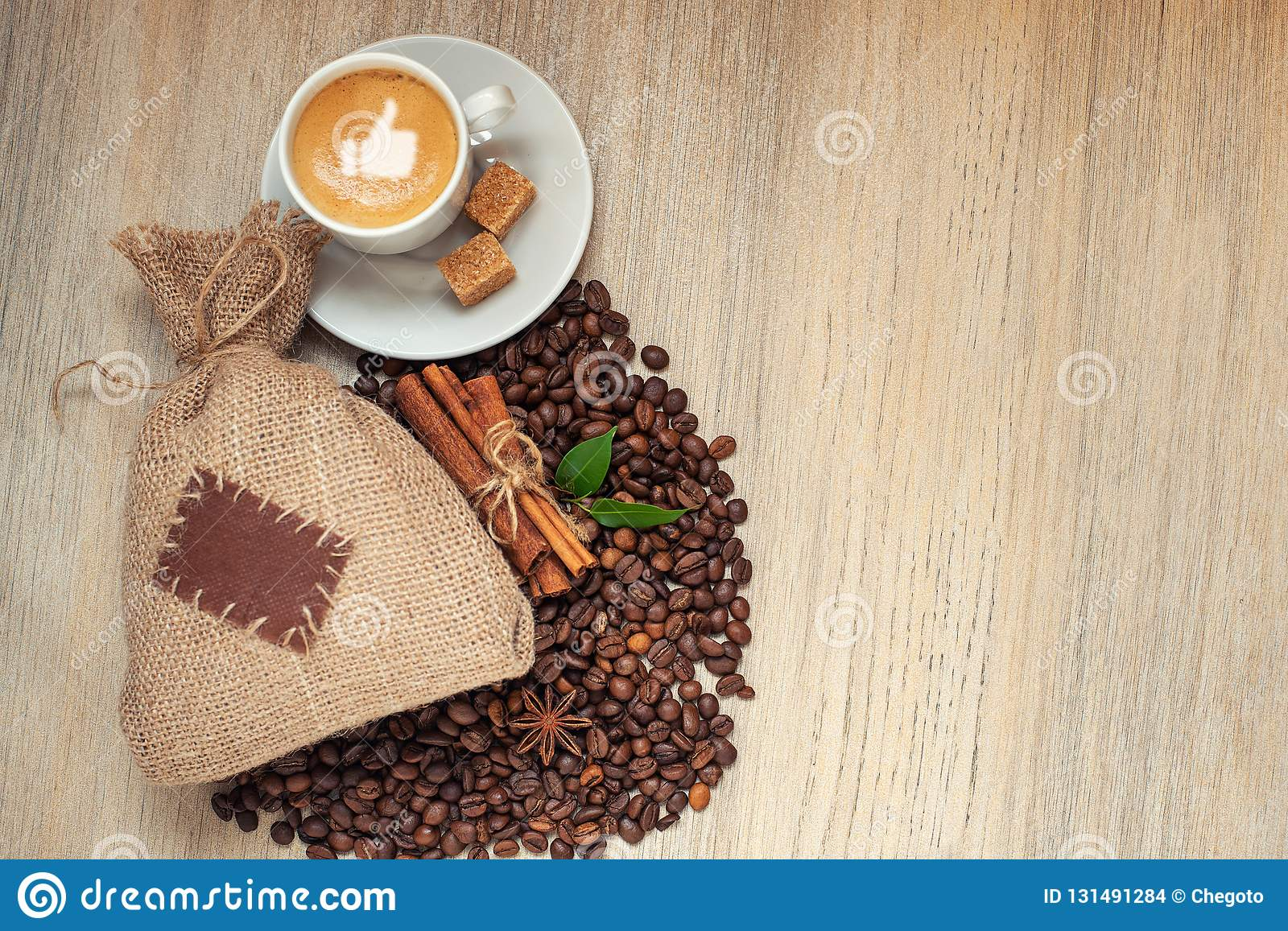 Cup with espresso with coffee beans, burlap sack and cinnamon on light wooden background. With like sign on coffee foam