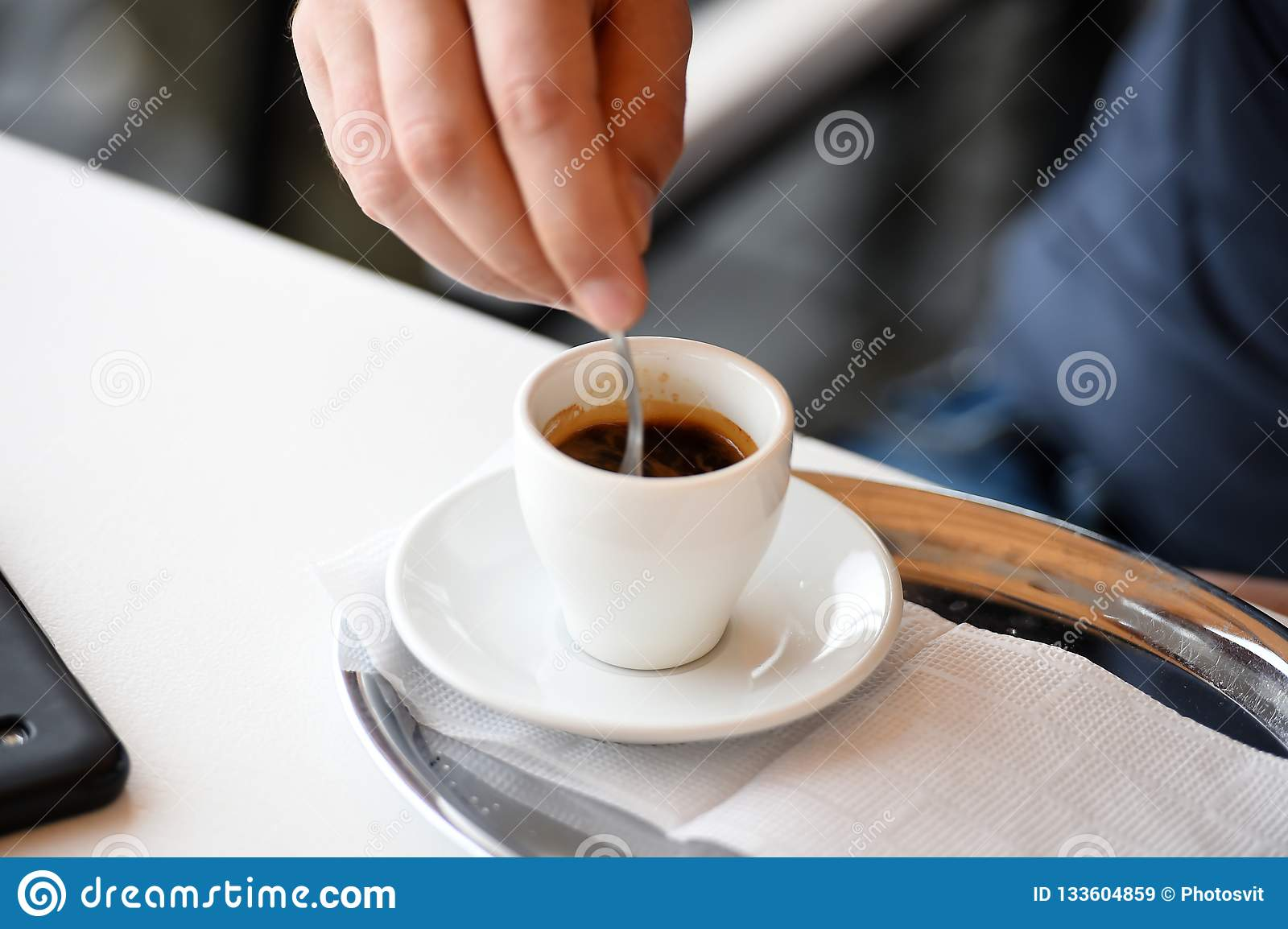 Cup espresso coffee on table with plate and spoon. Coffee time concept. Stir sugar in coffee cup. Male hand hold spoon