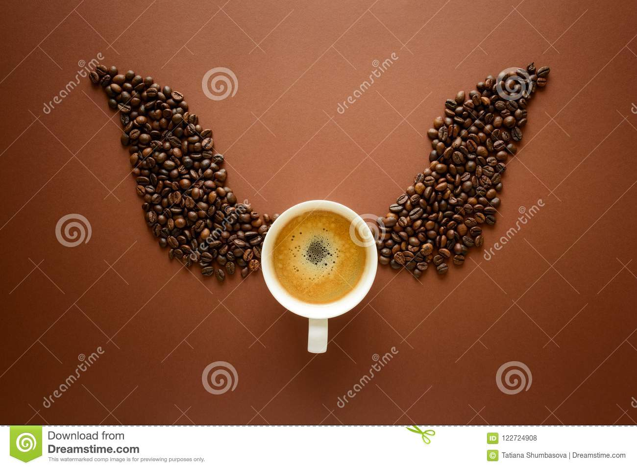 Cup of espresso with wings from coffee beans on brown background. Good morning concept. Top view. Flat lay.