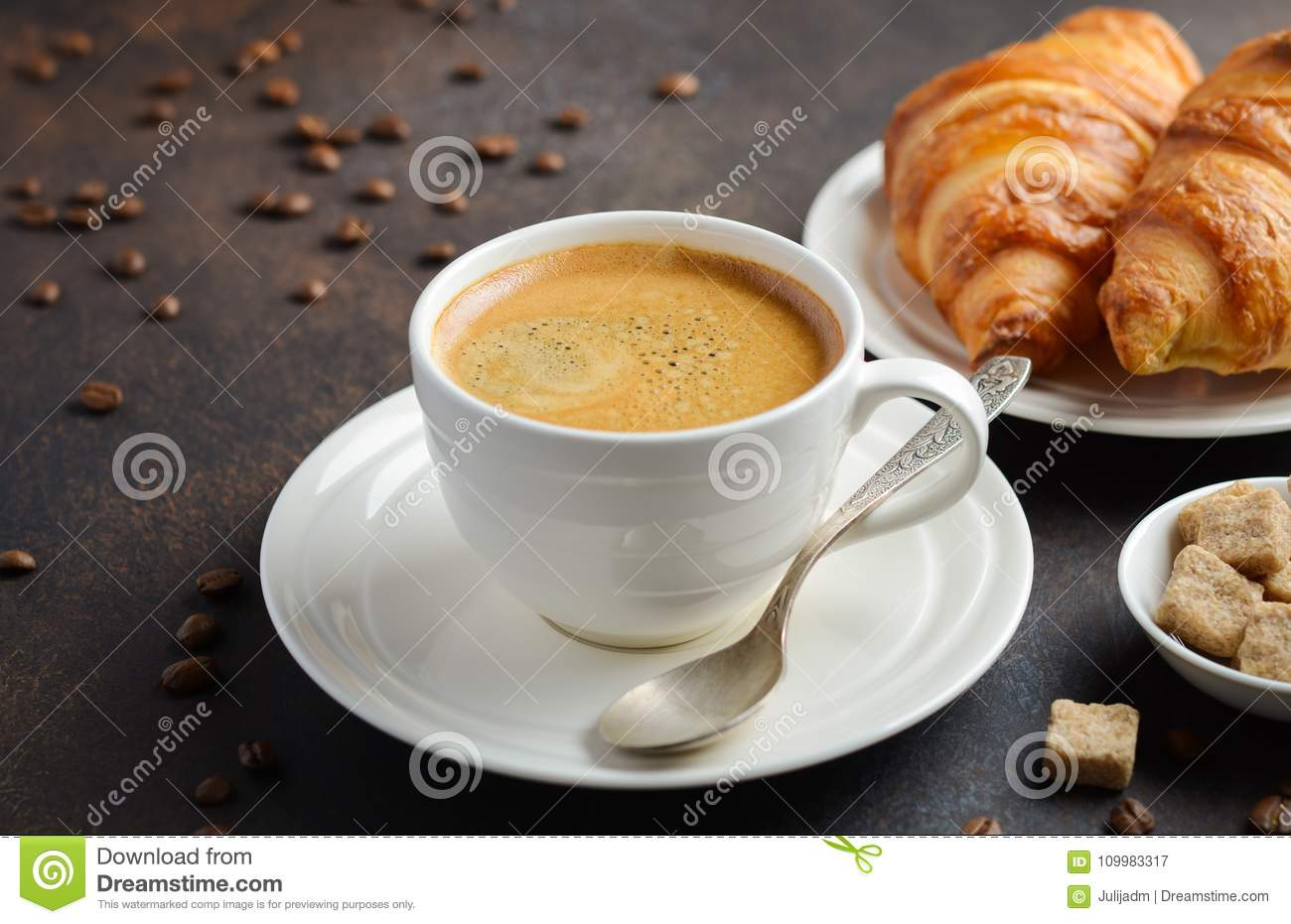 Cup of fresh coffee with croissants on dark background