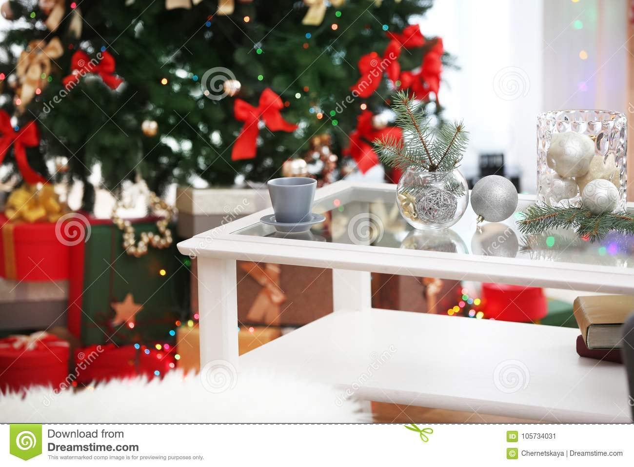 cup and glass vases with christmas decor on white table