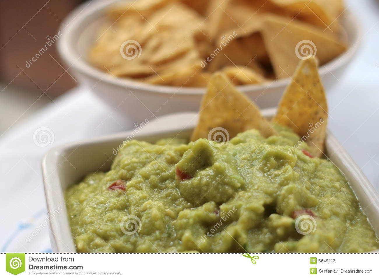 Cup of guacamole with blurred nachos in background