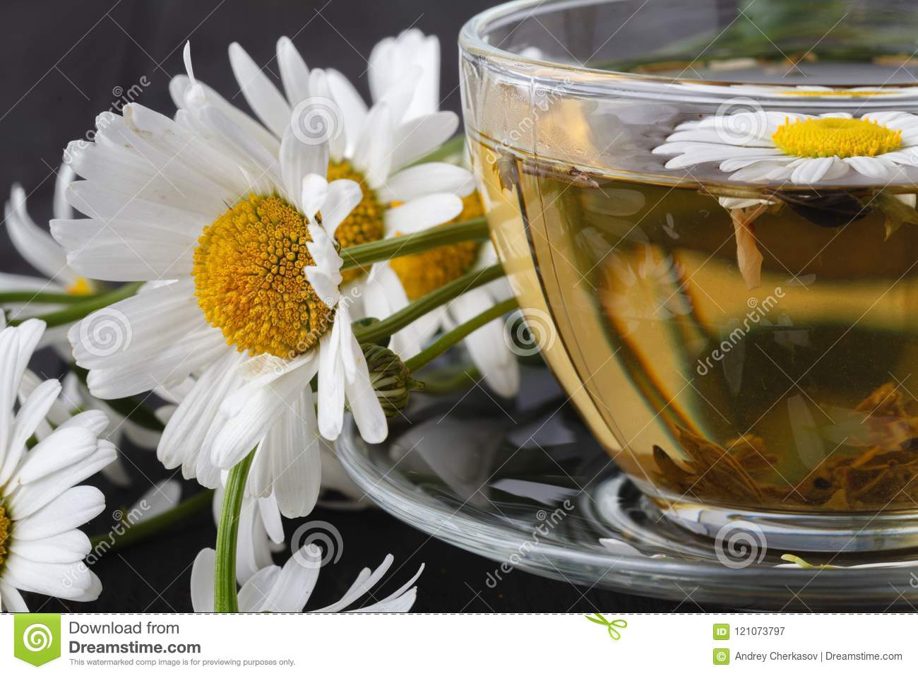 Cup Of Herbal Chamomile Tea With Fresh Daisy Flowers On Wooden