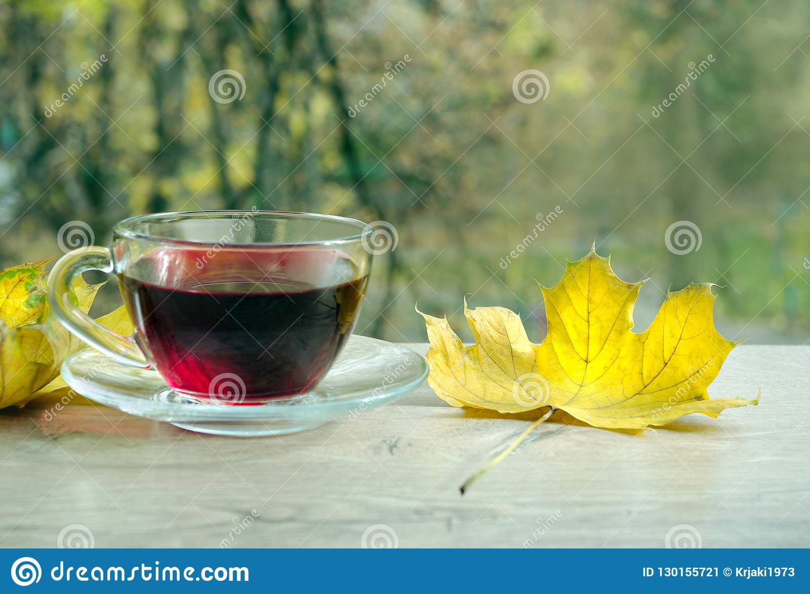 Cup Of Hibiscus Tea And Yellow Leaves On A Wooden Table Cup With