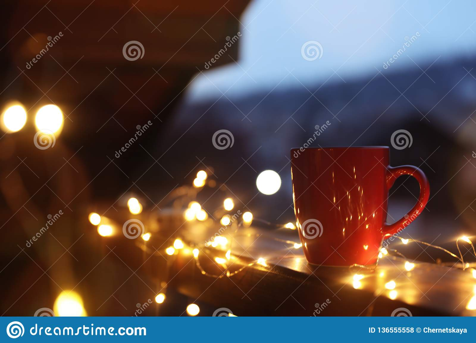 Cup of hot beverage on balcony railing decorated with Christmas lights, space for text. Winter
