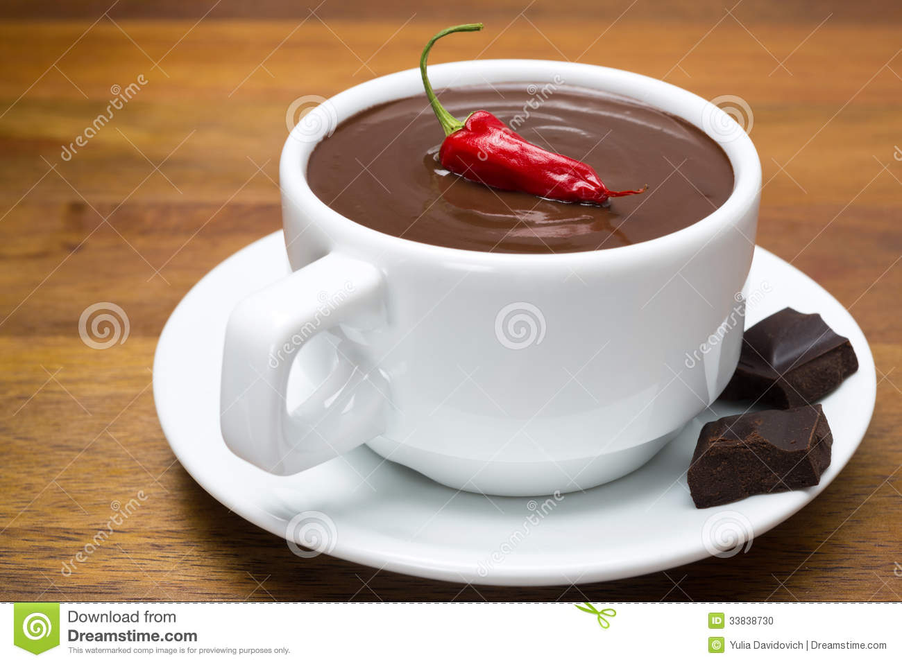 Cup of hot chocolate with chili peppers on a wooden background, close ...