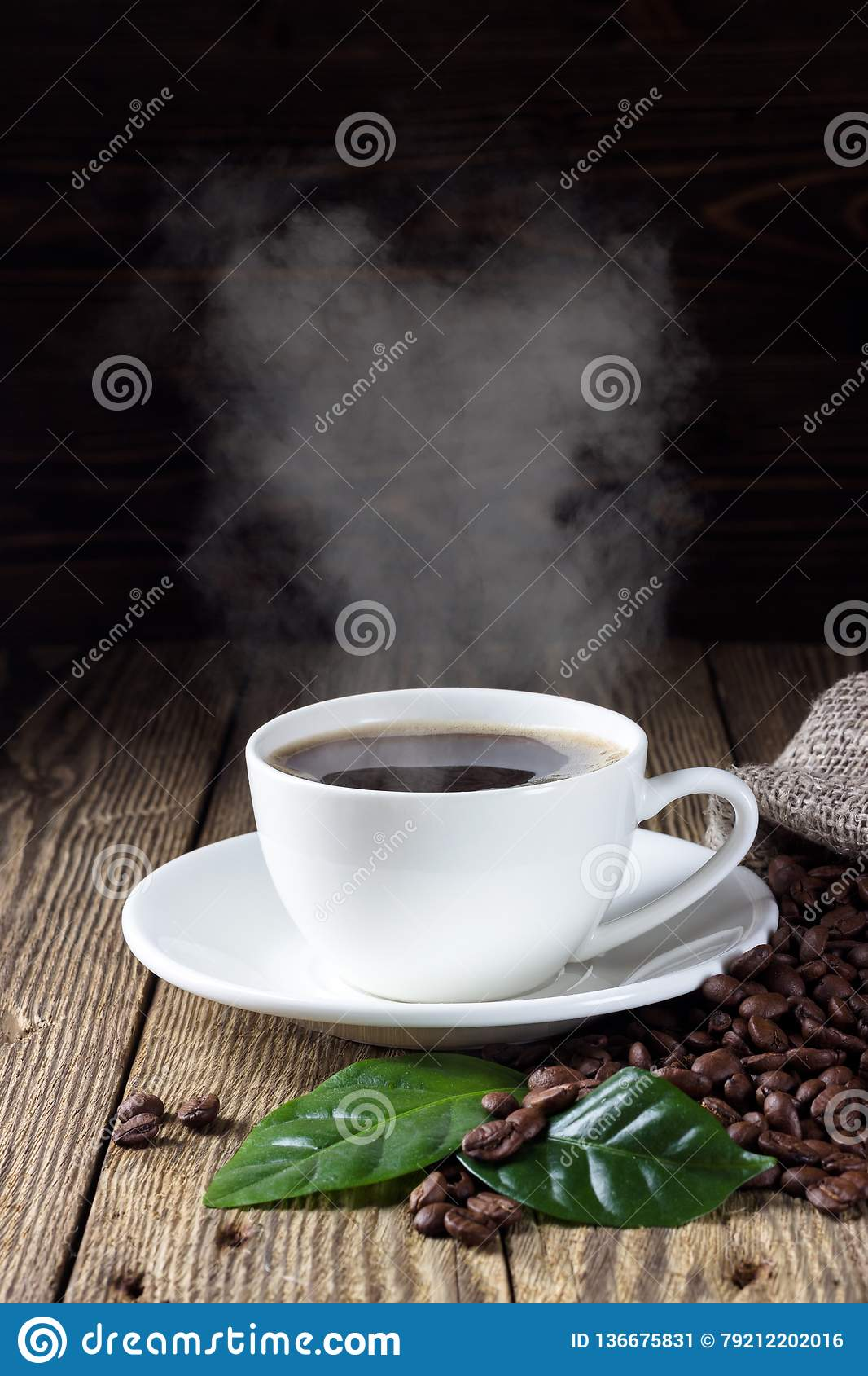 Cup of hot coffee with coffee beans and leaf