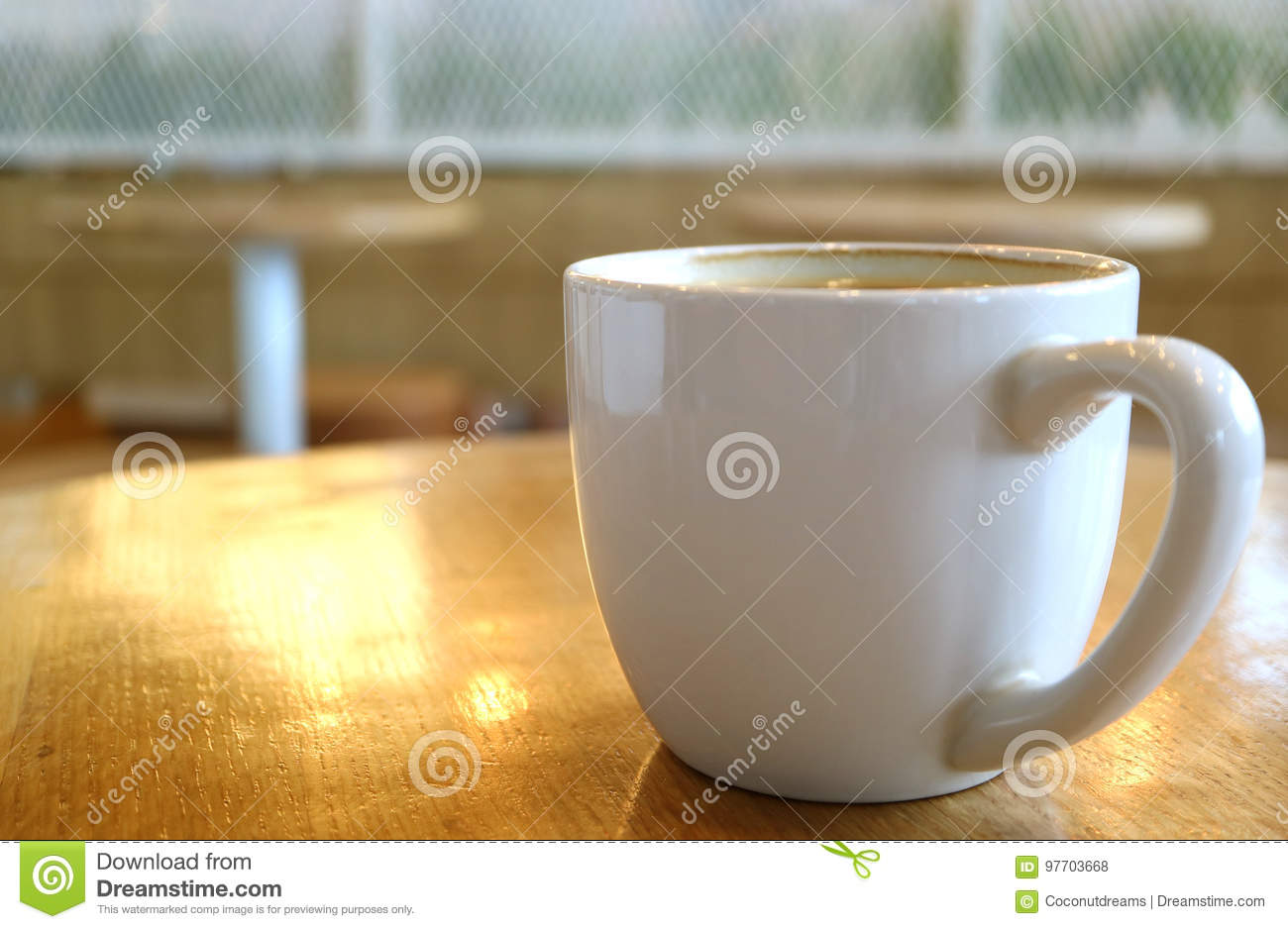 Cup of Hot Coffee on a Wooden Table with Sunlight Reflections