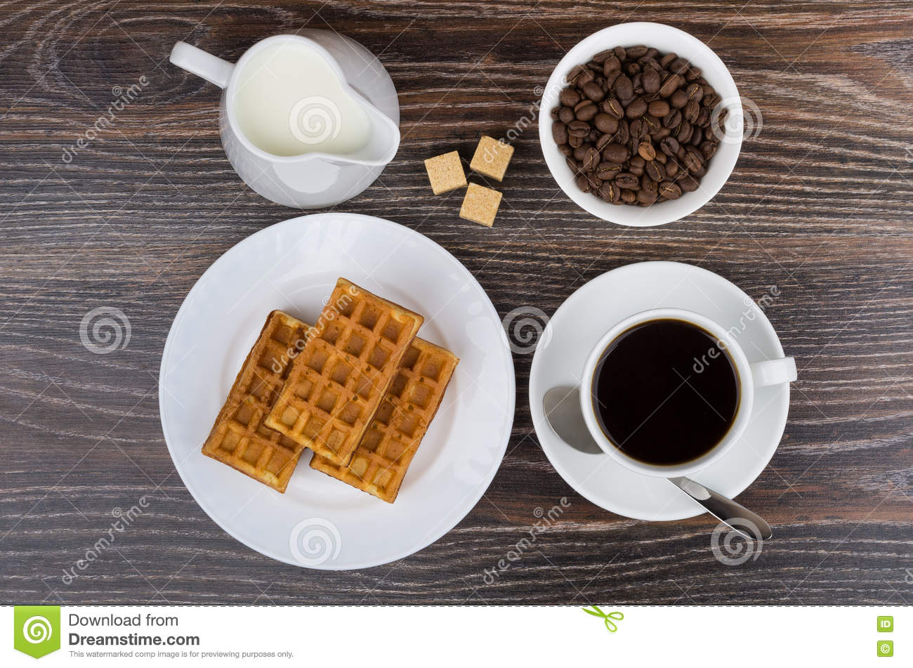 Cup, jug milk, bowl with coffee beans and viennese waffles