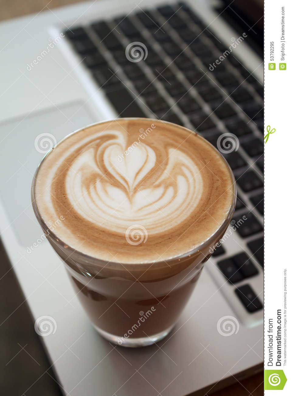 A Cup of latte coffee on laptop keyboard