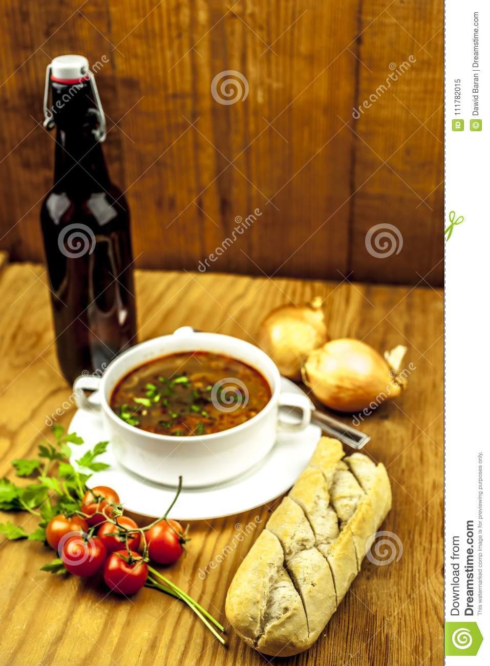 Cup of onion soup with beer and tomatoes, onion and baguette