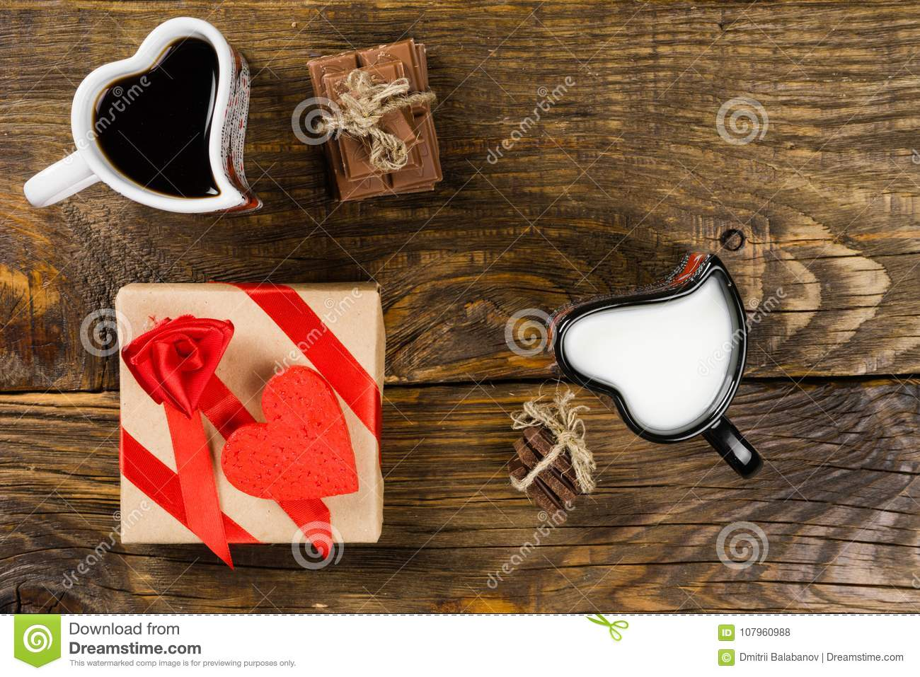 Cup in the shape of hearts, one poured coffee in the other milk, next the chopped chocolate twine tied around the decorative heart