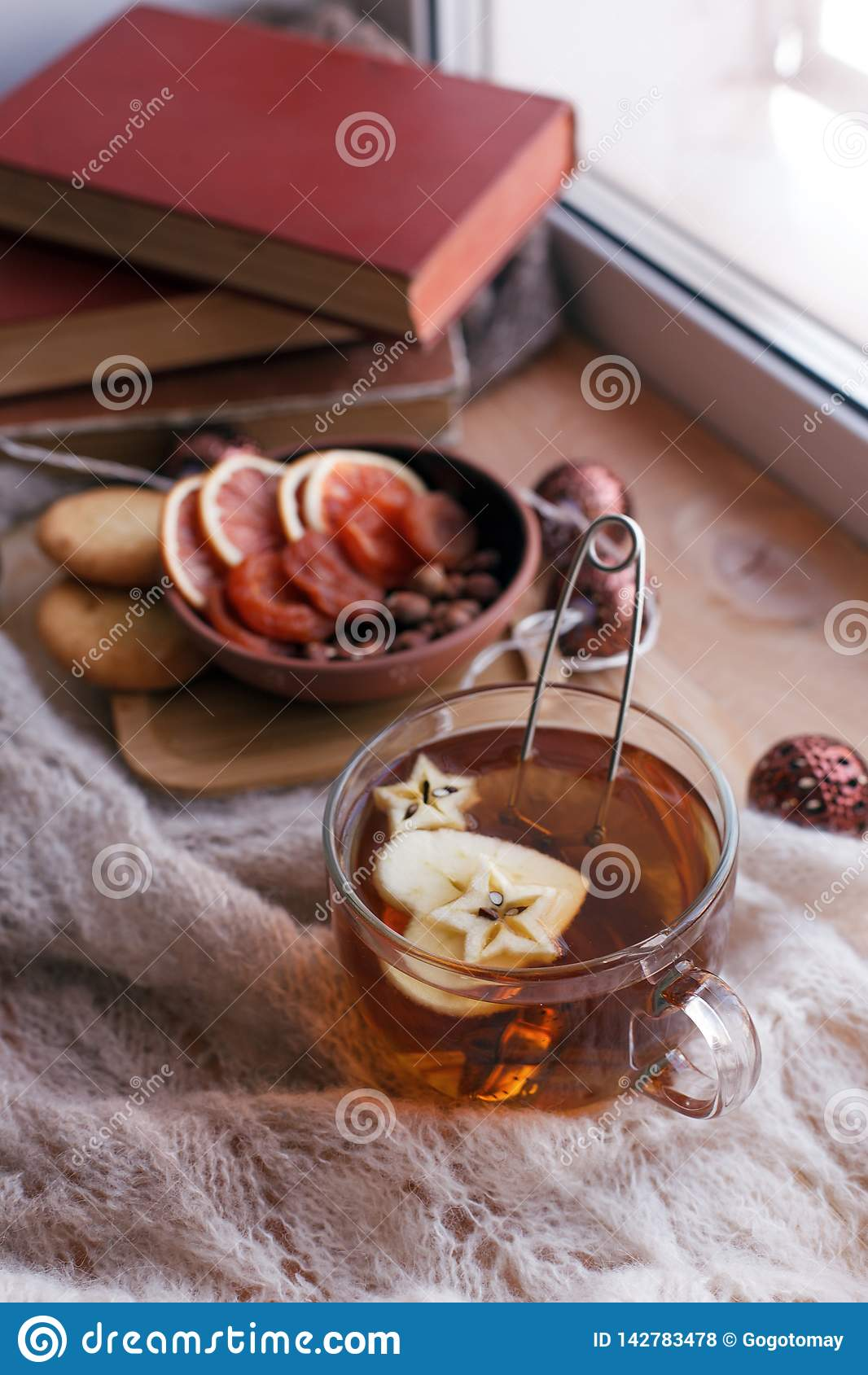 Cup of tea with apple, knit a blanket, dried fruit and books on the window sill, concept of cozy homely weekend, relax, tea party