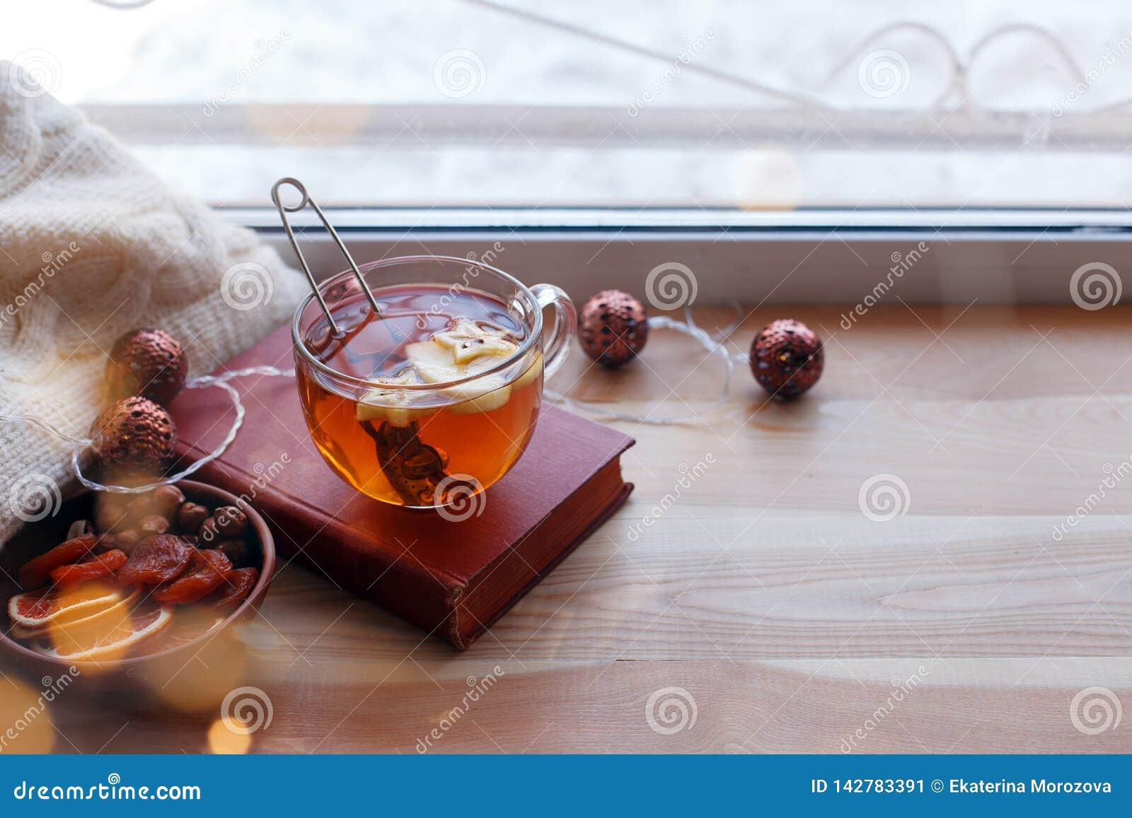 Cup of tea, book, warm pillow, garland light on wooden window sill, Moody seasonal still life. Warm tones, horizontal, copy space