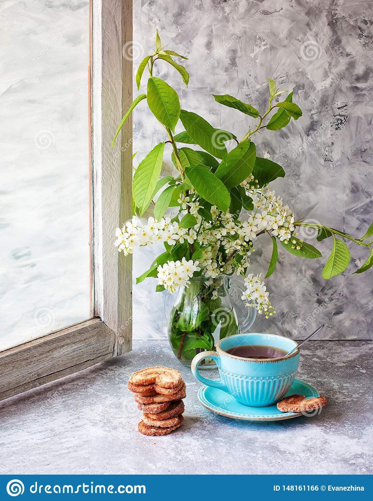 Cup of tea, cookies, bird cherry bouquet in a glass vase on a gray table. The Berlin cookies. Spring. Tea drinking. Front view