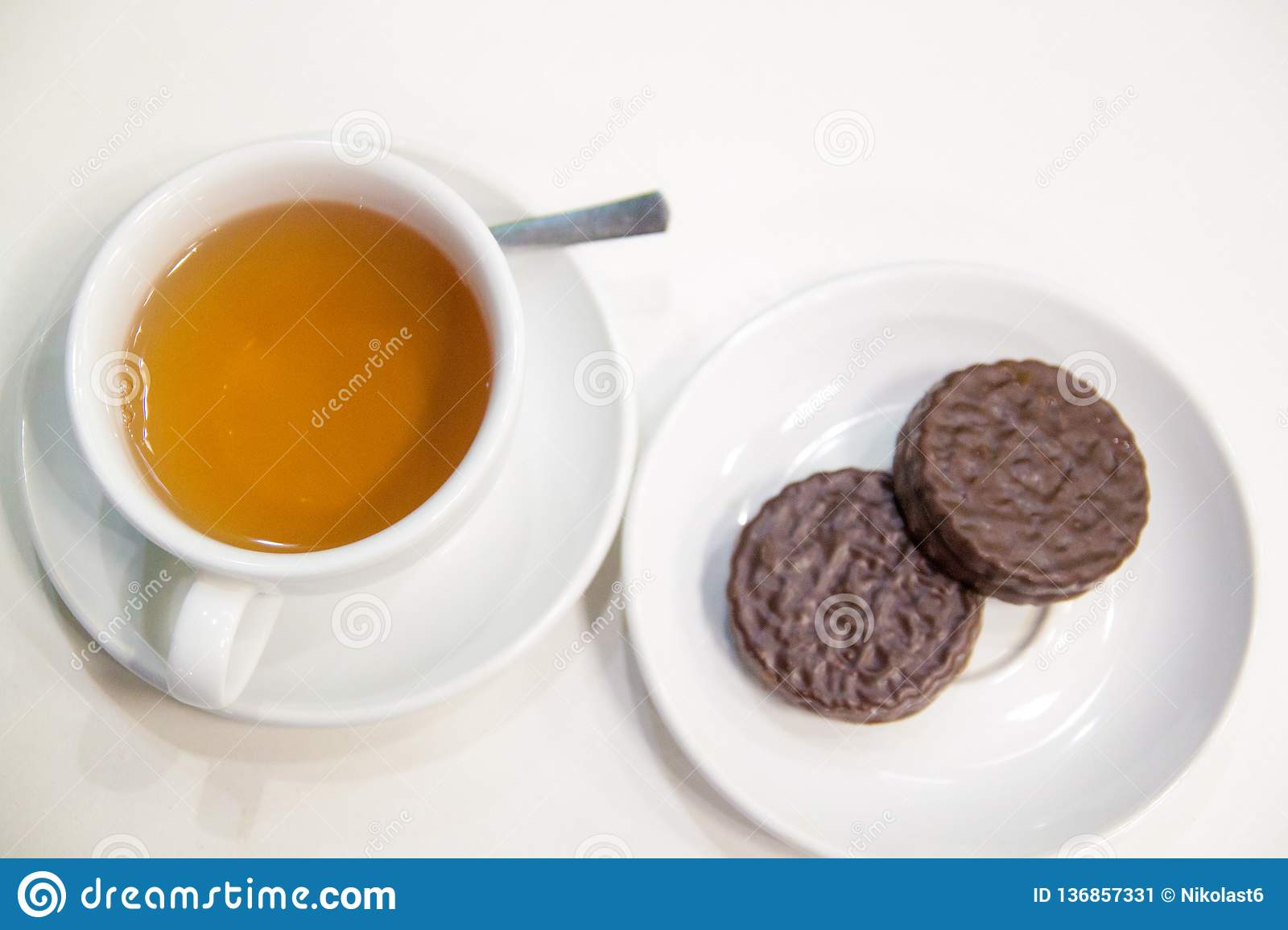 A cup of tea and cookies on the table in white background