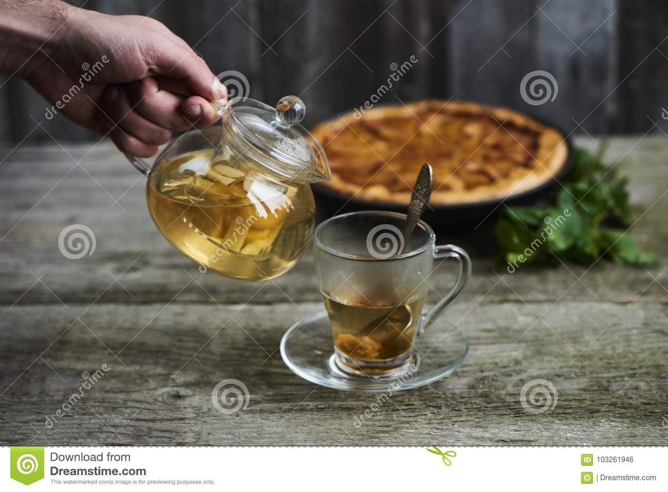 A cup of tea with homemade apple quince pie on rustic wooden background