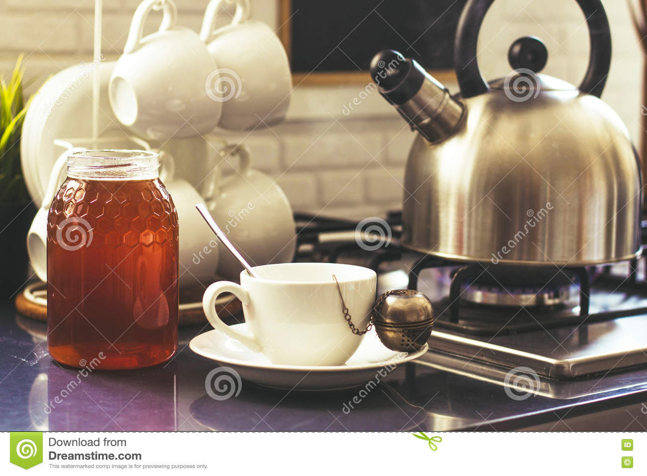 A Marble In A Cup Of Honey : Cup of tea with honey on the table stock photo image