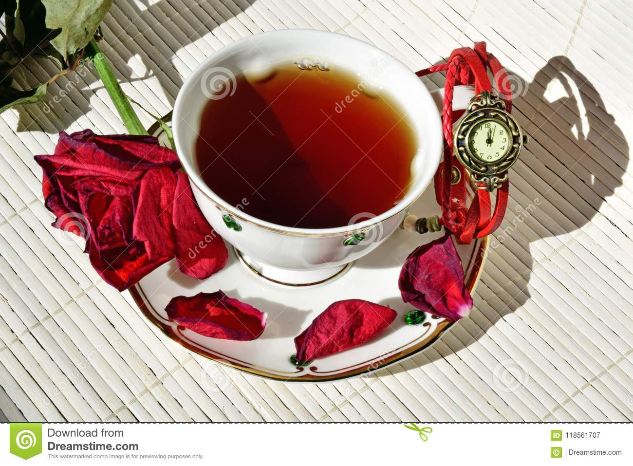 Cup Of Tea  On The Saucer Are Scattered Dry Rose Petals