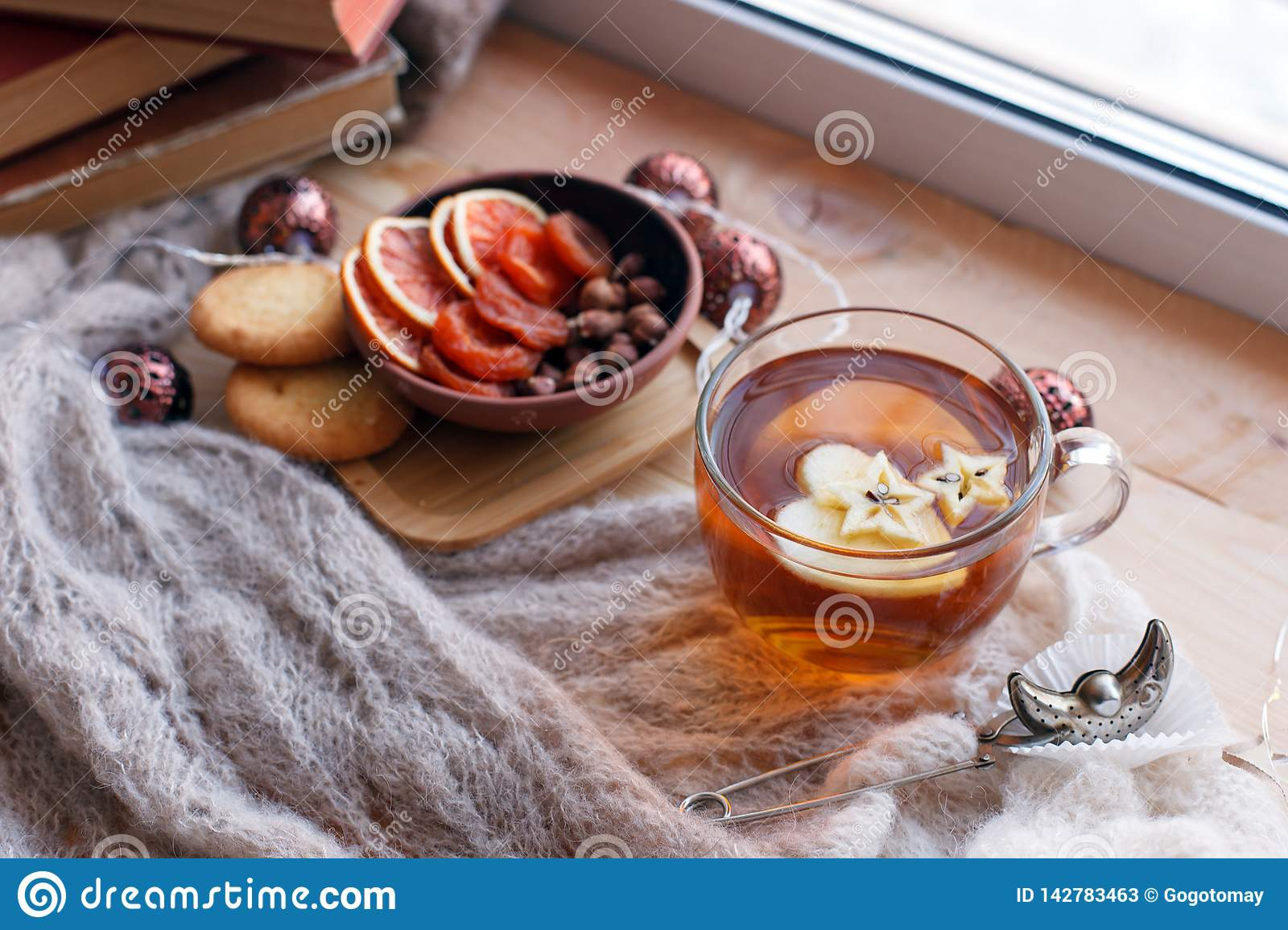 Cup of tea, snacks, book and warm blanket on windowsill, close up, relax unplug background, seasonal homely weekend, love to read