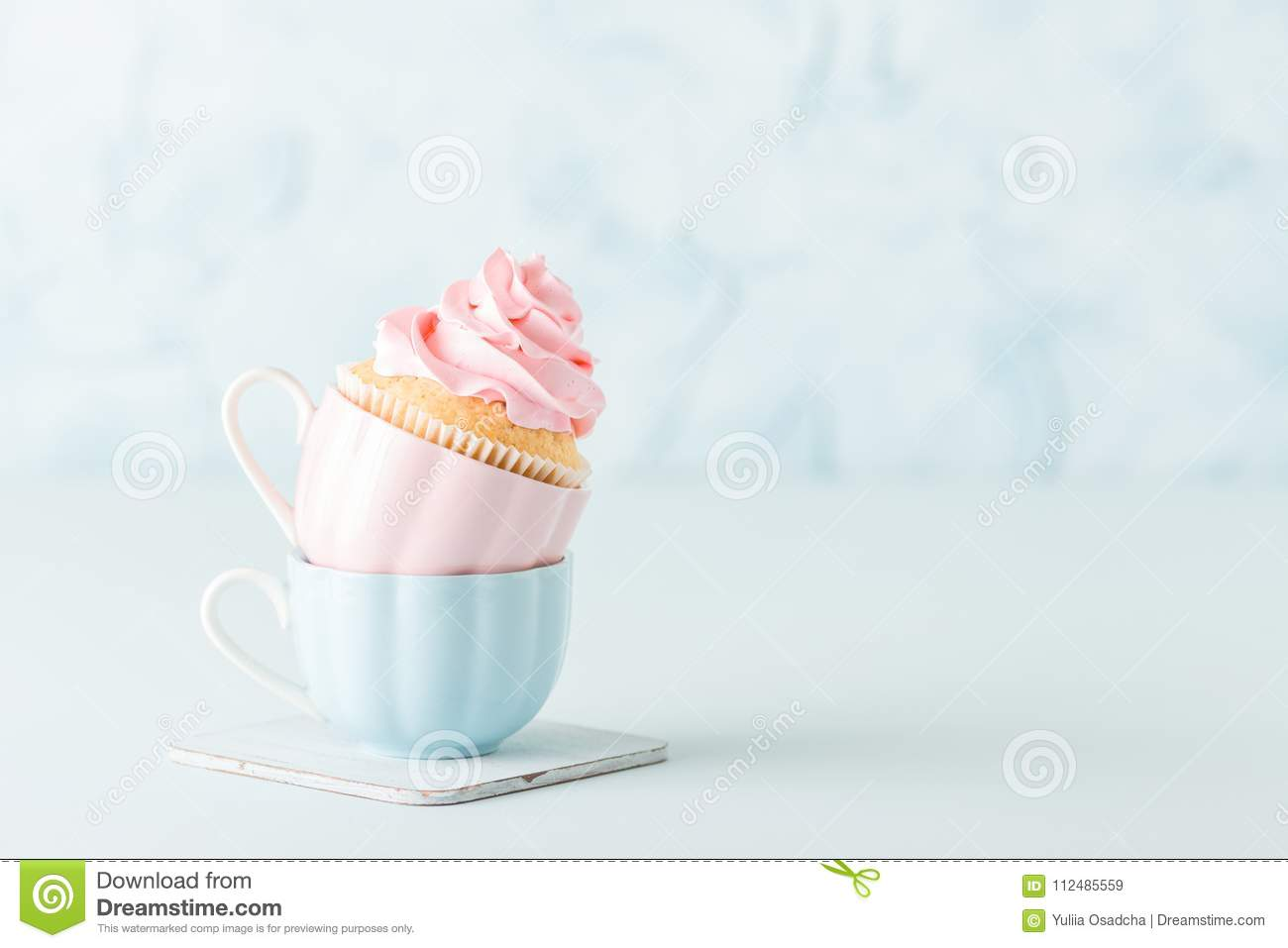cupcake with gentle pink cream decoration in two cups on blue pastel