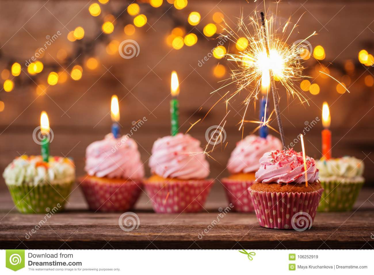 Cupcake with sparkler on old wooden background