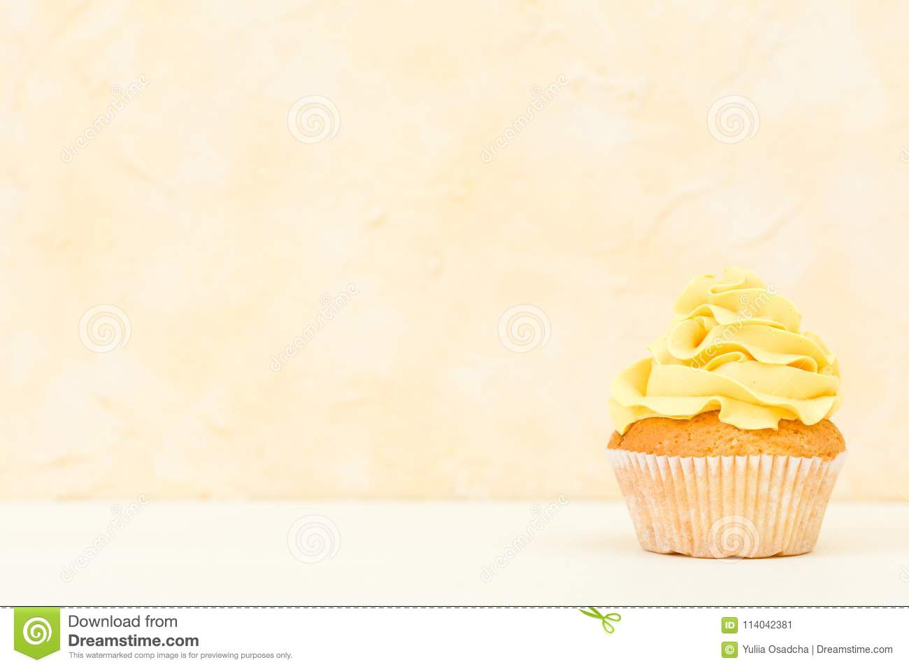 cupcake with yellow cream decoration on yellow background pastel