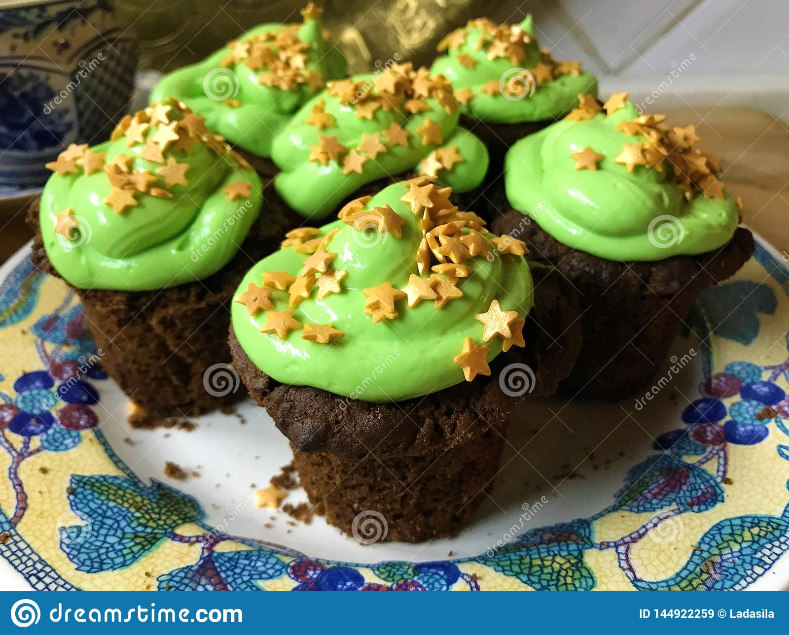 Cupcakes with green frosting and golden stars sprinkles on a white plate
