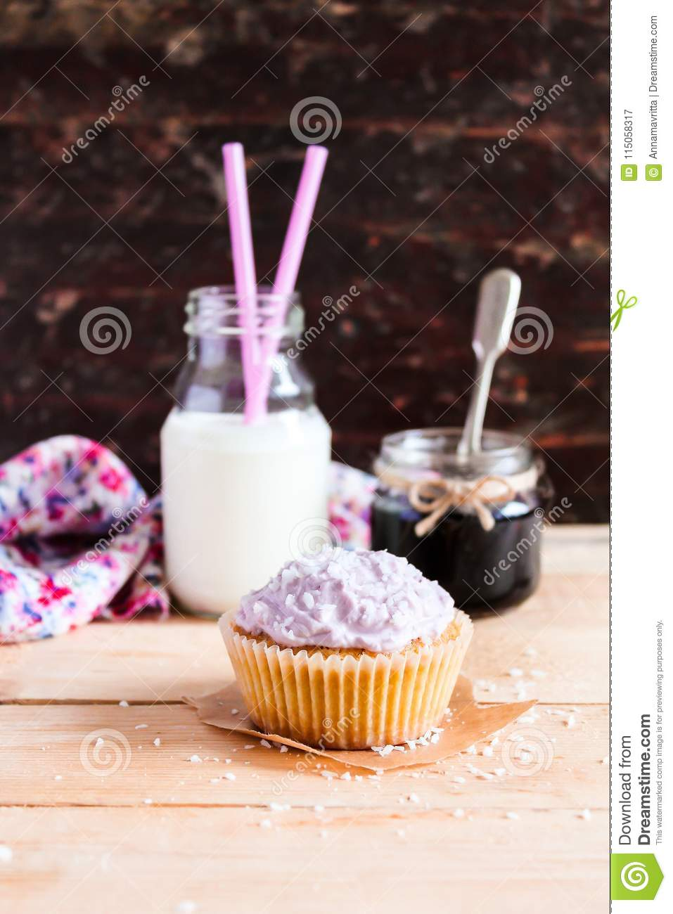 Cupcakes with mascarpone cream cheese, black currant jelly jam and freshly shredded coconut on a wooden table with a bottle of mil