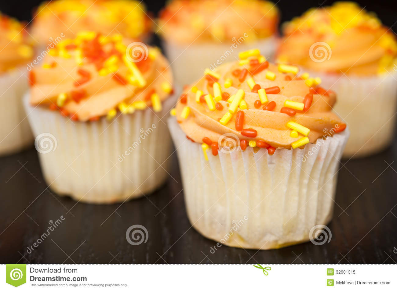 Cupcake with orange icing and yellow and orange sprinkles.