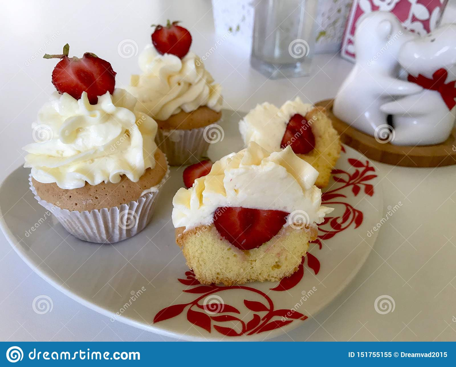 Cupcakes with strawberries and butter cream. One of them is cut, the filling is visible. On a white surface with decorative