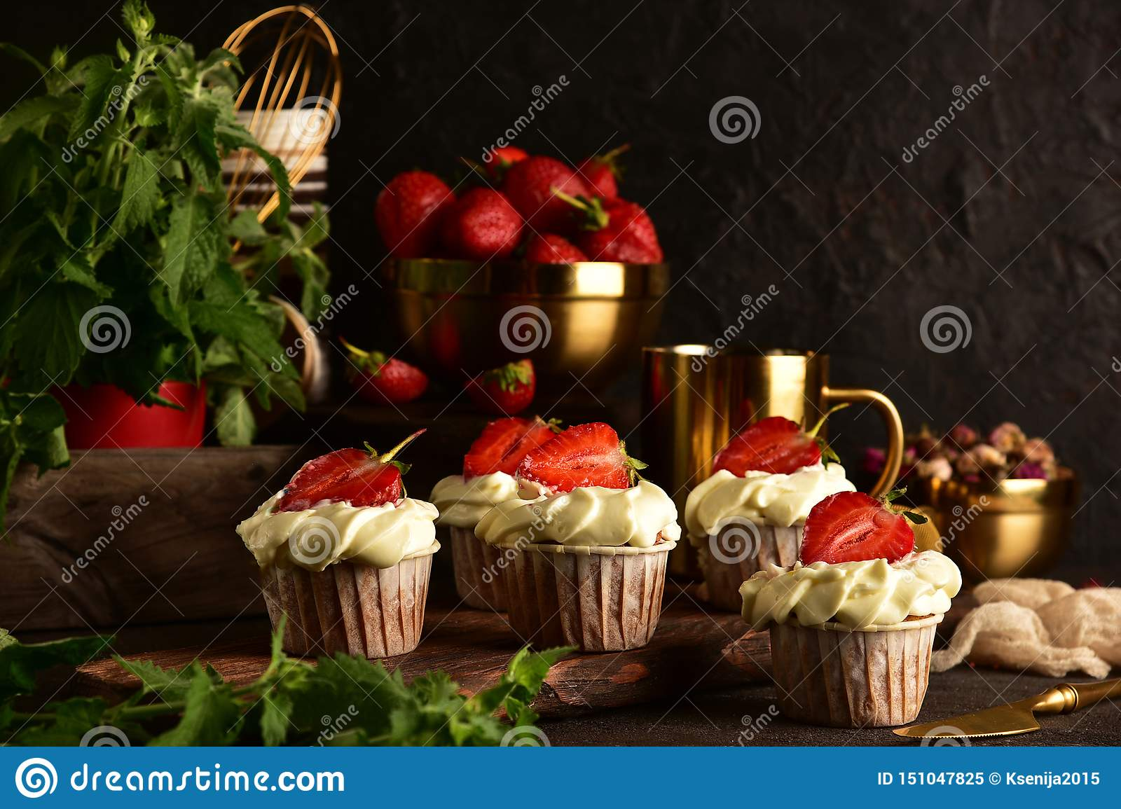 Cupcakes with strawberries on a dark background. Still life
