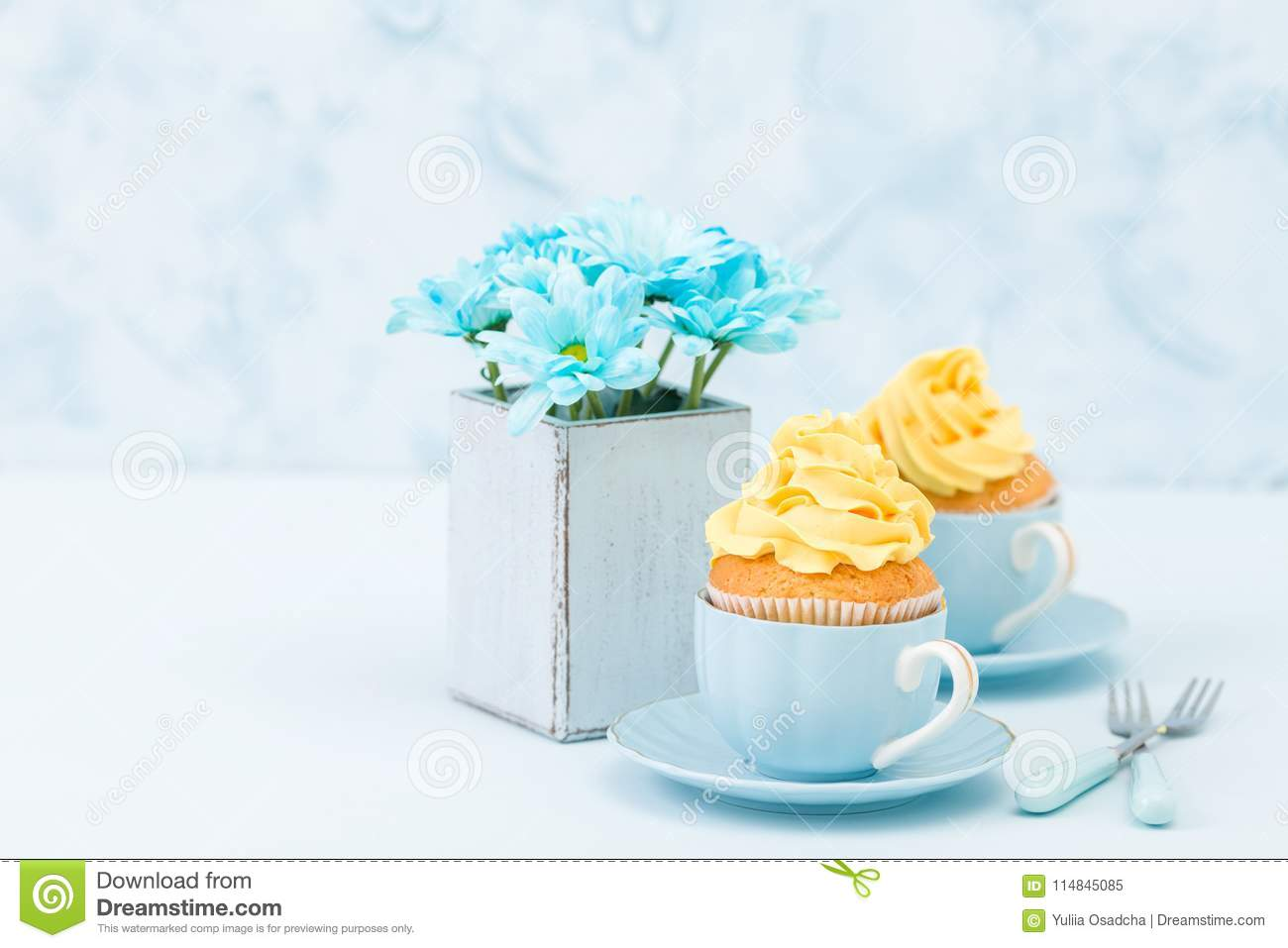 Cupcakes With Tender Yellow Cream Decoration And Bouquet Of Blue ...