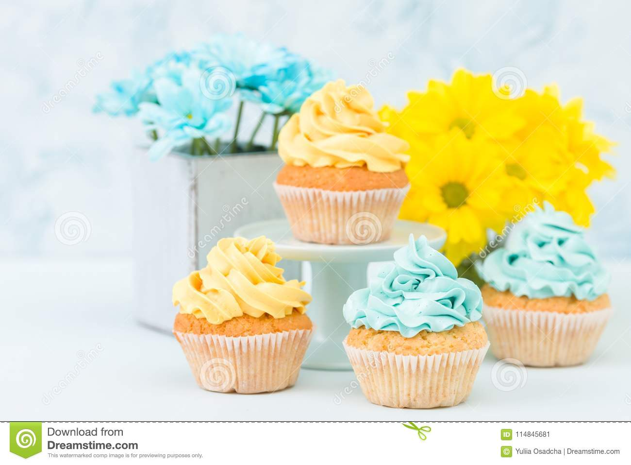 Cupcakes With Yellow And Blue Cream Decoration And Bouquets Of ...