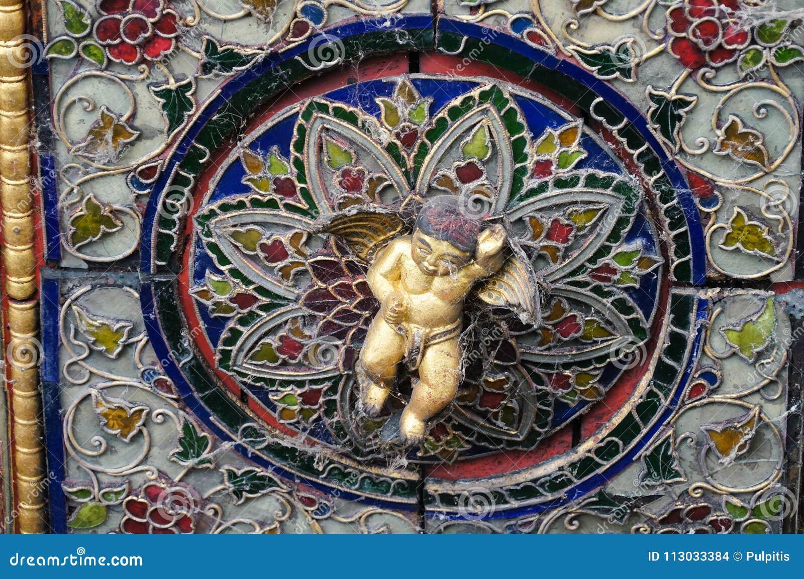 Cupido precioso en el techo de Wat Phra Kaew Don Tao, Lampang, Thail