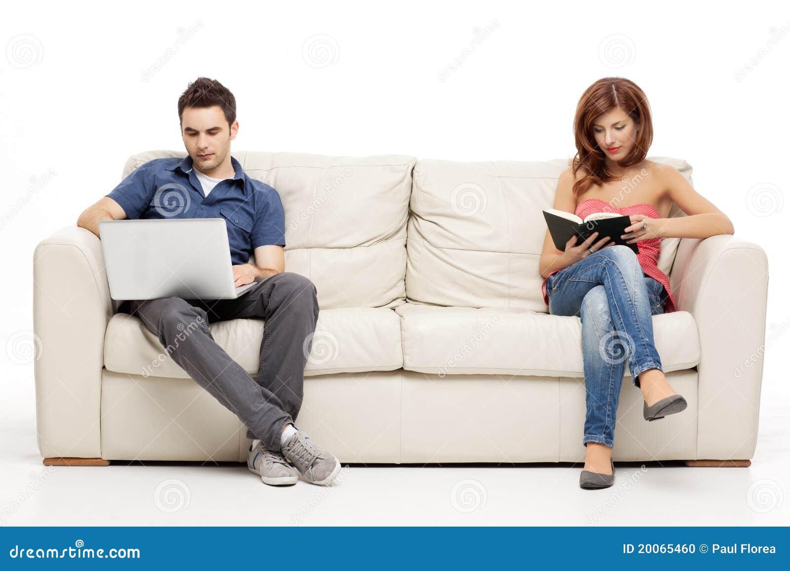 Cuple se reposant avec le livre et l ordinateur portatif