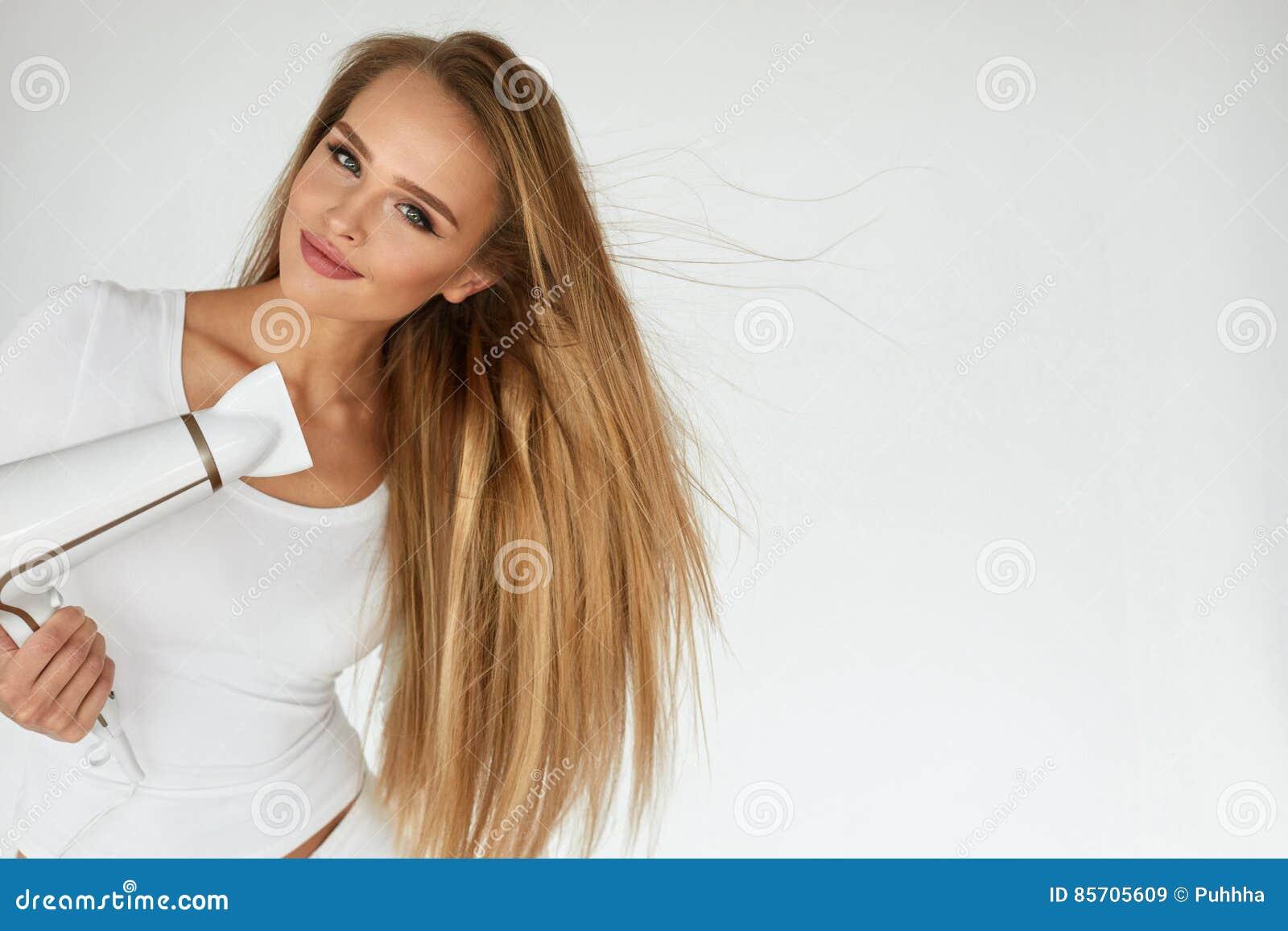 Cura di capelli Bella donna sorridente che asciuga capelli diritti lunghi  sani facendo uso del fon Ritratto della ragazza attraente con capelli biondi  ... ffaed190030