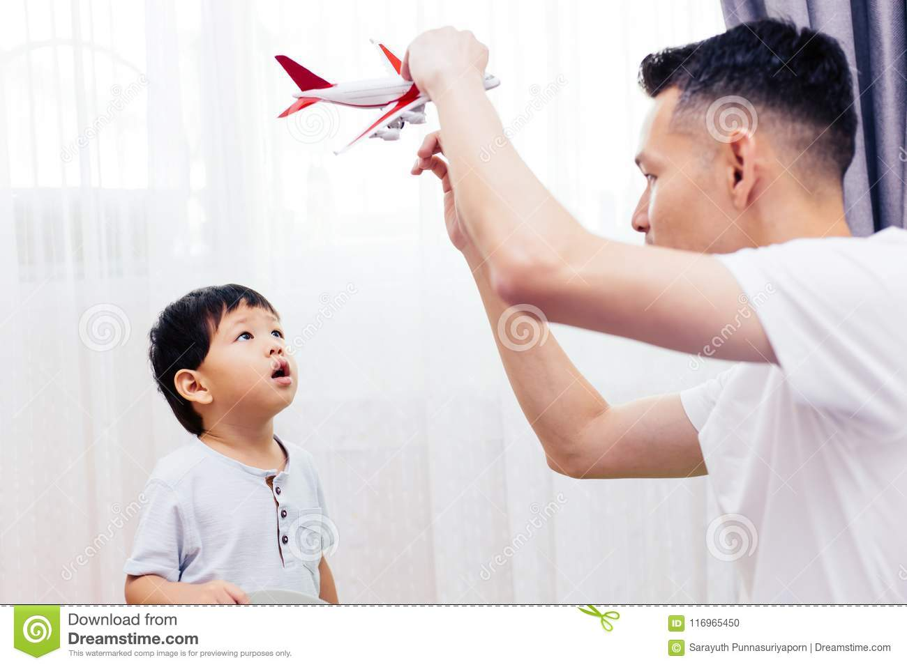 Curious kid looking at the plane toy and playing with father. Asian family playing toys together at home.