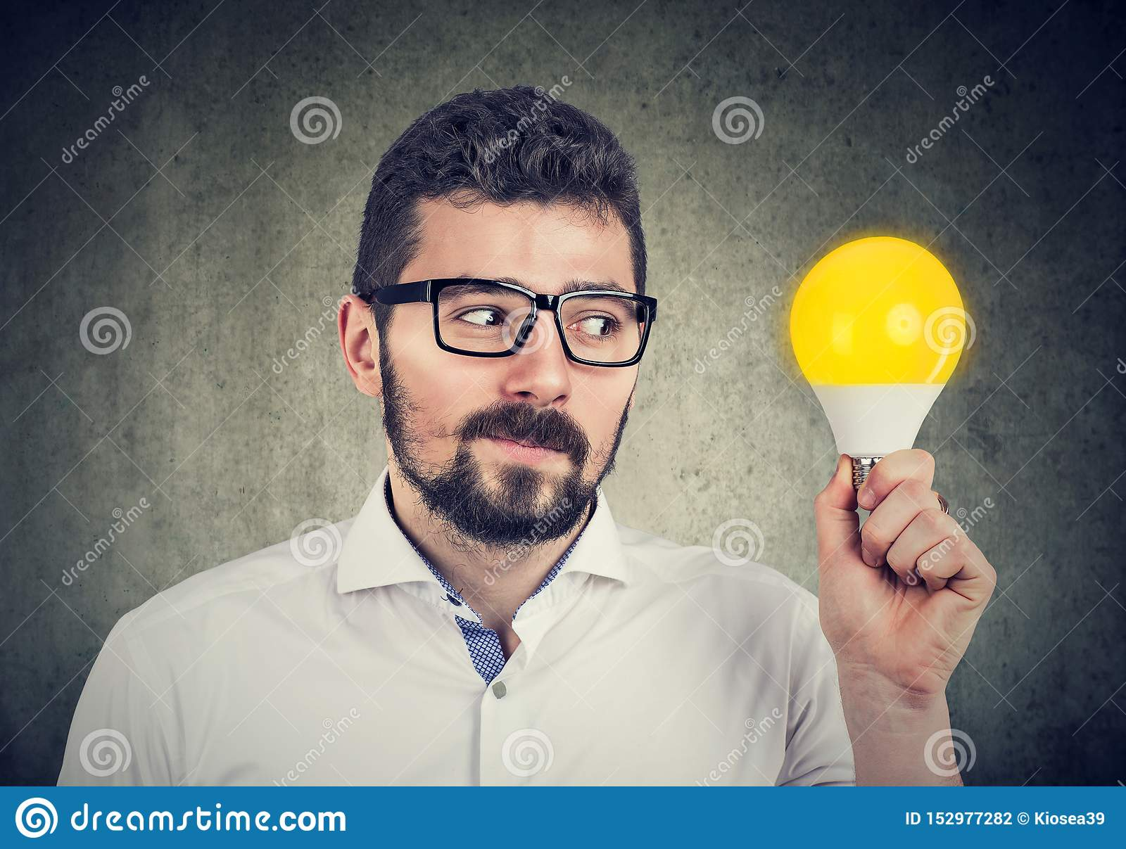 Curious man holding looking at bright light bulb