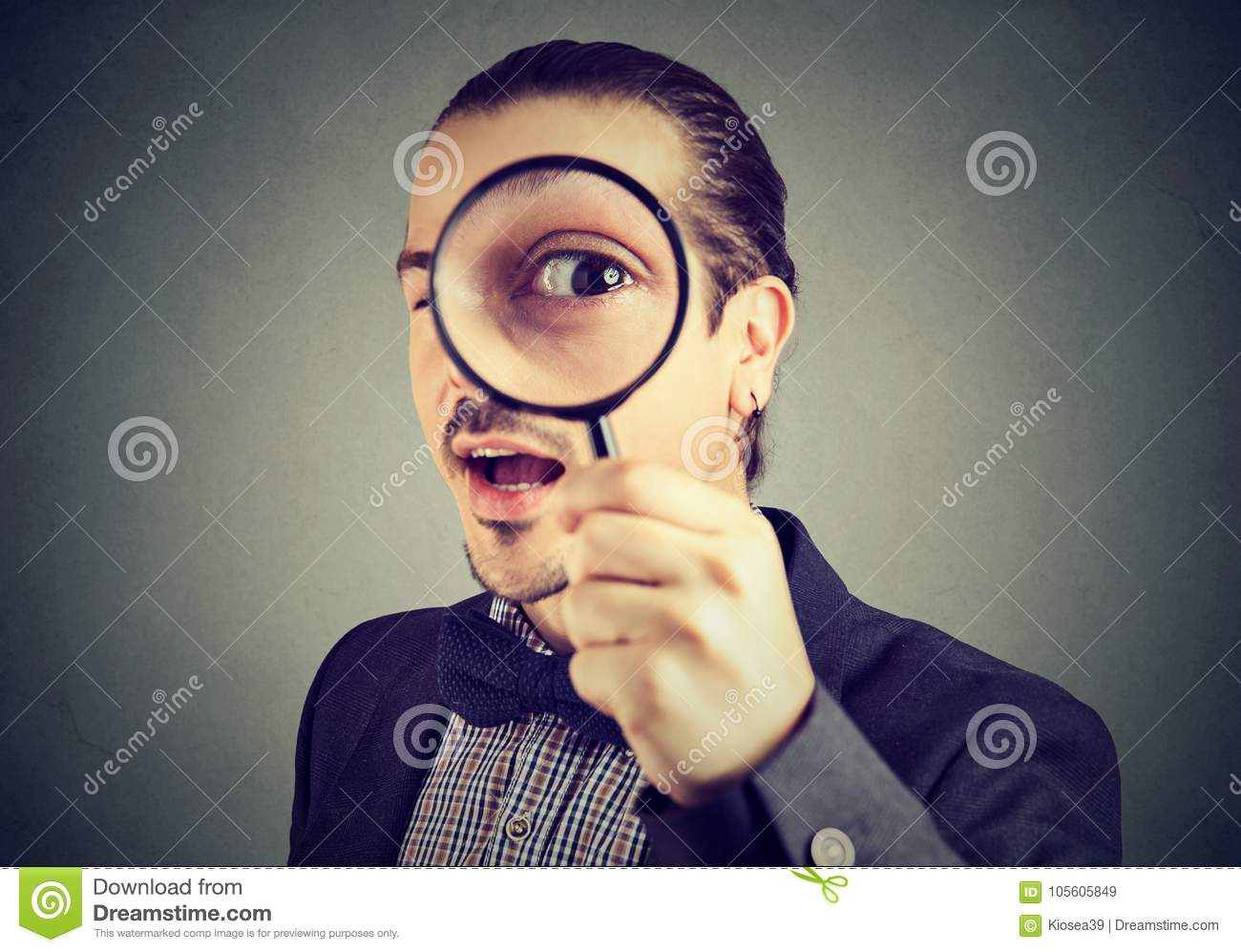 Curious young business man looking through a magnifying glass