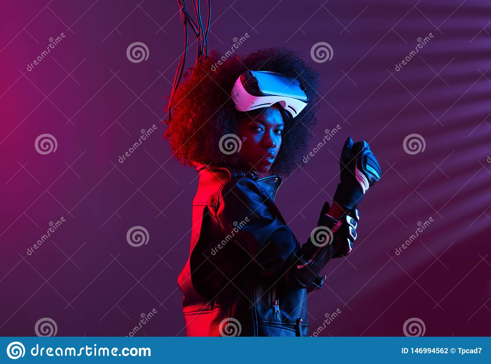 Curly dark haired girl dressed in a black leather jacket and gloves is wearing the virtual reality glasses on her head