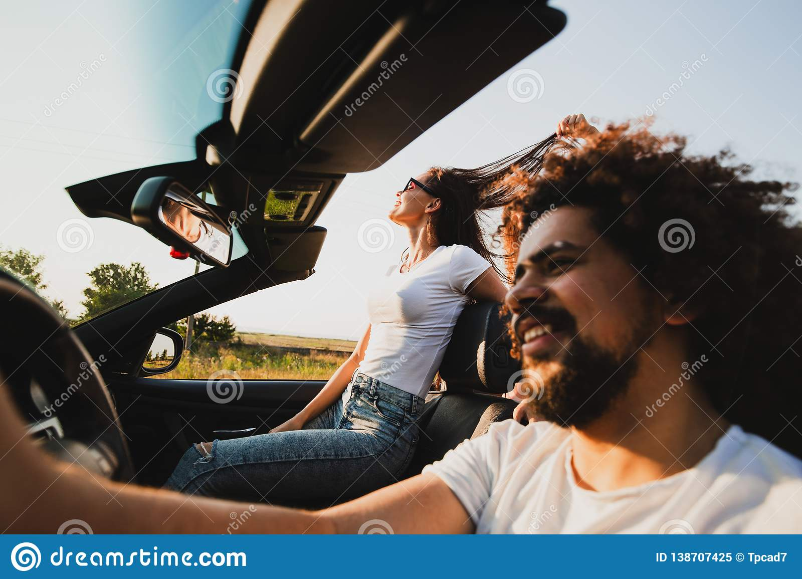 Curly dark-haired young man sitting at the wheel of a black cabriolet and beautiful woman is sitting next to him on a