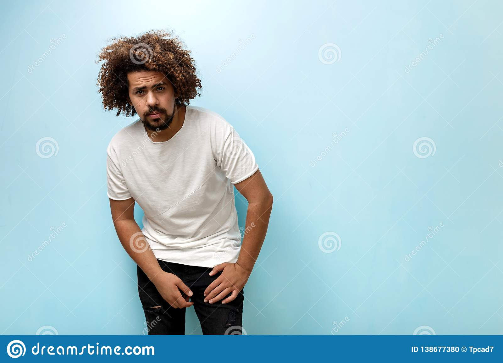 A curly-headed brunet man is leaning forwards wearing white T-shirt and ripped jeans. The guy is holding hands on the