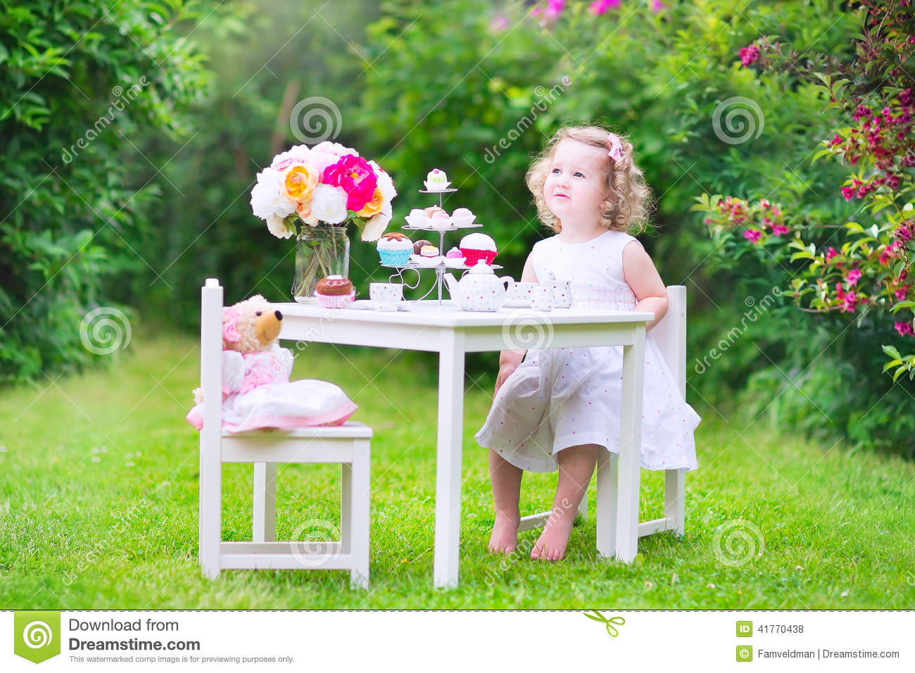 Curly Toddler Girl Playing Tea Party With A Doll Stock