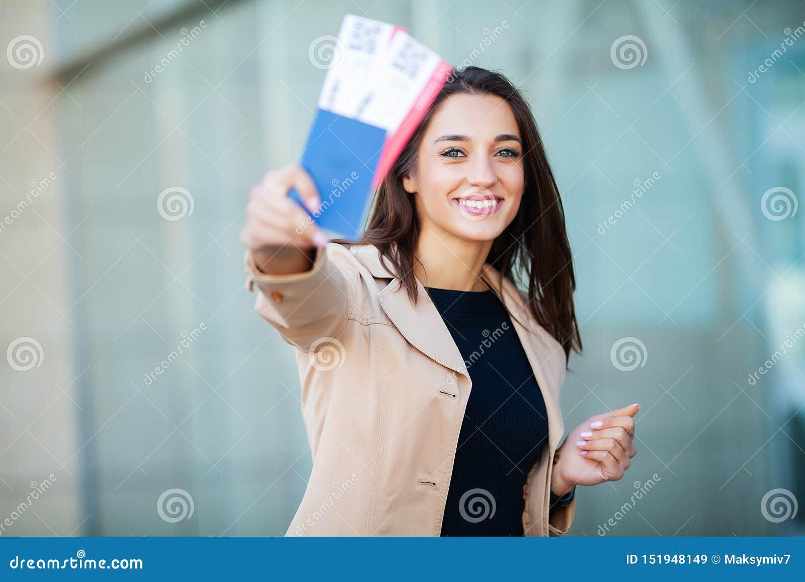 Curso Bilhete de ar da terra arrendada dois da mulher no exterior no passaporte perto do aeroporto