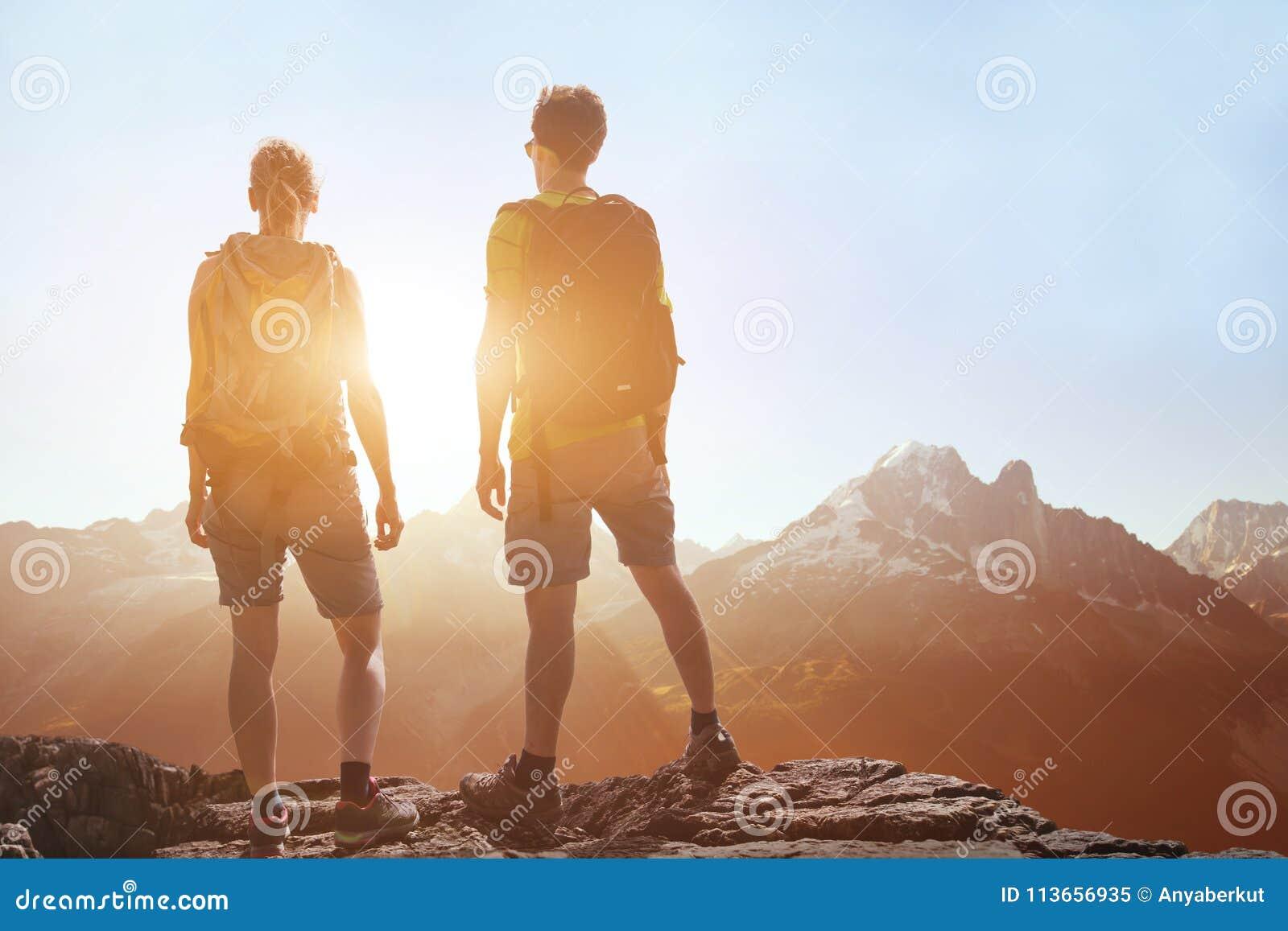 Curso, viagem dos povos, caminhando nas montanhas, pares de caminhantes que olham a paisagem panorâmico