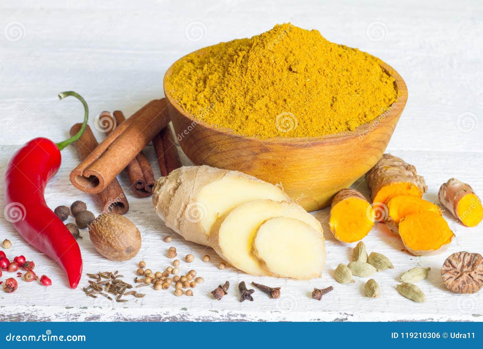 Curta receta de la especia del masala la vieja de los ingredientes indios del polvo en los tableros blancos